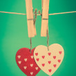 Two heart ornaments hanging from pegs on a line - Stock Photo