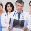 Doctor holding x-ray with his team — Stock Photo #24117983
