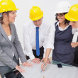 Team looking at a construction plan and laughing  — Stock Photo