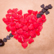 Heart and arrow shaped from candy and chocolate - Stock Photo