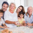 Smiling family baking together — Stockfoto #24118143