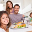 Family smiling at the camera at dinner table - Stock Photo
