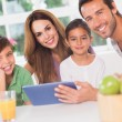 Stock Photo: Happy family using a tablet pc