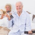 Elderly man lifting hand weights — Stock Photo