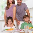 Photo: Two children and their parents smiling at the camera at dinner t