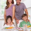 Two children and their parents smiling at the camera at dinner t — Stockfoto #24118243