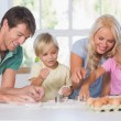 Family cutting the dough — Stock Photo