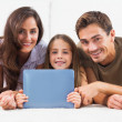 Family with tablet lying on a carpet - Stock Photo