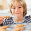 Smiling boy holding a cookie — Stock Photo