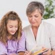 Little girl and her grandmother reading a book — Stockfoto