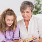 petite fille et sa grand-mère, lisant un livre — Photo
