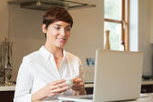 Woman using laptop and drinking coffee — Stock Photo