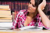 Kobieta myśli w bibliotece — Zdjęcie stockowe