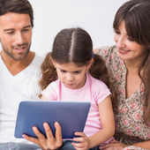 Os pais assistindo filha usando o tablet pc — Fotografia Stock