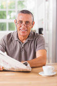 Smiling man reading a newspaper — Stock Photo