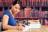 Cute girl writing on notebook in library — Stock Photo