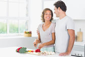 Husband embracing wife as she prepares vegetables — Stock Photo