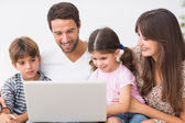 Smiling family using laptop on couch — Stock Photo