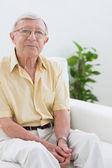 Elderly man sitting on the sofa — Stock Photo