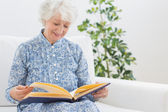 Elderly smiling woman looking at photos — Stock Photo