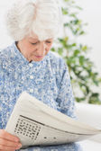 Elderly focused woman reading newspapers — Stock Photo