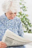 Elderly focused woman reading newspapers — Stock Photo