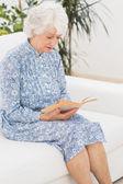 Elderly calm woman reading a old novel — Stock Photo