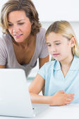 Mother and daughter using the laptop — Stock Photo