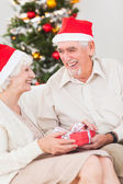 Elderly couple exchanging christmas gifts — Stock Photo