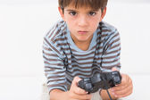 Boy playing his game console — Stockfoto