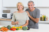 Happy couple cutting vegetables together — Stock Photo