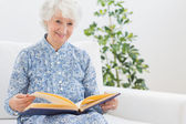 Elderly woman watching pictures — Stock Photo