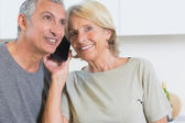 Cheerful mature couple listening a call together — Stock Photo