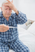 Old man taking his temperature — Stock Photo