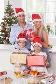 Family holding christmas presents — Stock Photo