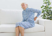 Elderly woman suffering with back pain — Stock Photo