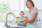 Happy mother and daughter doing the washing up — Stock Photo