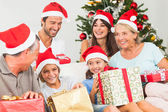 Happy family at christmas swapping gifts — Stock Photo