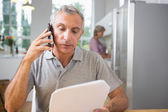 Focused man calling with a sheet of paper — Stock Photo