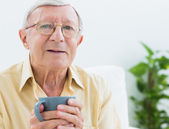 Elderly man with a cup — Stock Photo