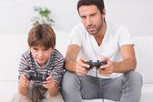 Vader en zoon spelen van videospellen — Stockfoto
