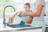 Daughter helping mother do the washing up — Stock Photo