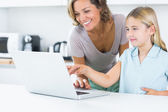 Happy mother and daughter using laptop — Stock Photo