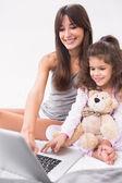 母亲和女儿与泰迪熊一起使用的笔记本电脑 — 图库照片