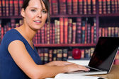 Woman smiling with computer — Stock Photo