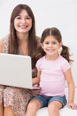 Smiling mother and daughter with laptop — Stock Photo
