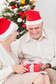 Elderly couple swapping christmas presents — Stock Photo