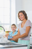 Mother washing up with daughter drying — Stock Photo