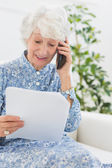 Elderly happy woman reading a paper on the phone — Stock Photo