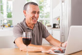 Happy man using laptop with glass of red wine — Stock Photo
